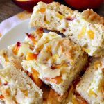 Peach Cobbler Cheesecake Brownies   Can't Stay Out of the Kitchen   these spectacular #brownies start with a #peachcobbler #cookie dough. They have a luscious #cheesecake filling in the middle, topped with fresh #peaches. Then more cookie dough is crumbled over top. These were a huge hit at my husband's office. #dessert #peachdessert #CANbassador #WashingtonStateFruitCommission #WashingtonStatestoneFruitGrowers