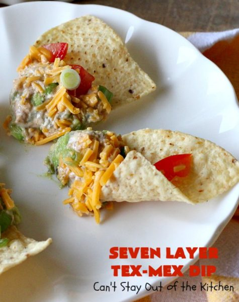 Seven Layer Tex-Mex Dip | Can't Stay Out of the Kitchen | this awesome #TexMex #dip is out of this world. It's terrific for any kind of company or #holiday party. We like it for #tailgating parties & potlucks. Also great for summer #holidays like #FourthOfJuly. #GlutenFree #Mexican #TexMexDip #LayeredMexicanDip #RefriedBeans #Jalapenos #Olives #CheddarCheese #Guacamole #TortillaChips #tomatoes #Avocados #SevenLayerTexMexDip #appetizer #TexMexAppetizer